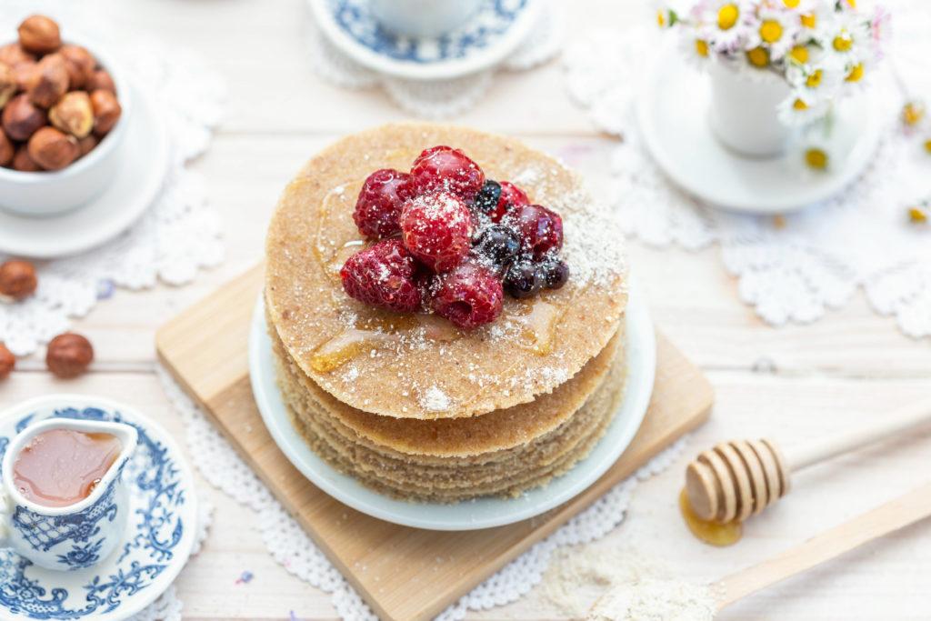 closeup of vegan pancakes with honey and berries