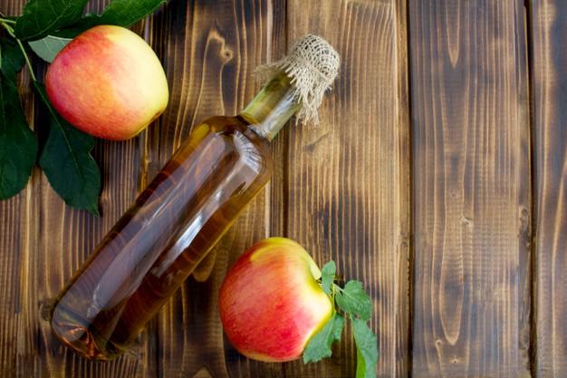 apple cider vinegar bottle with two apples