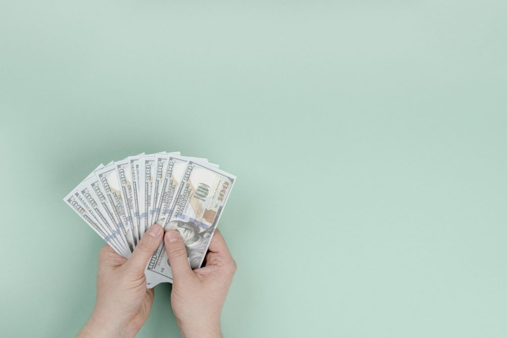 hand holding money on a green background