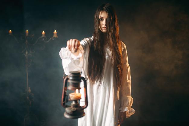 woman holding a kerosene lamp