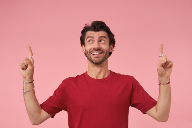 bearded male smiling with hands raised,pink background