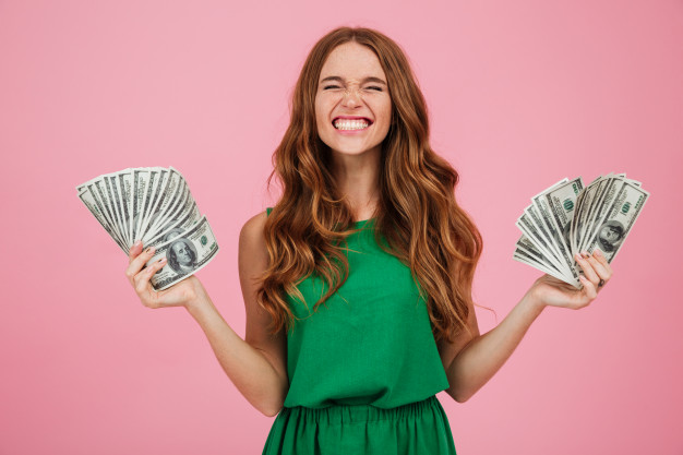 happy woman standing with money in her hands