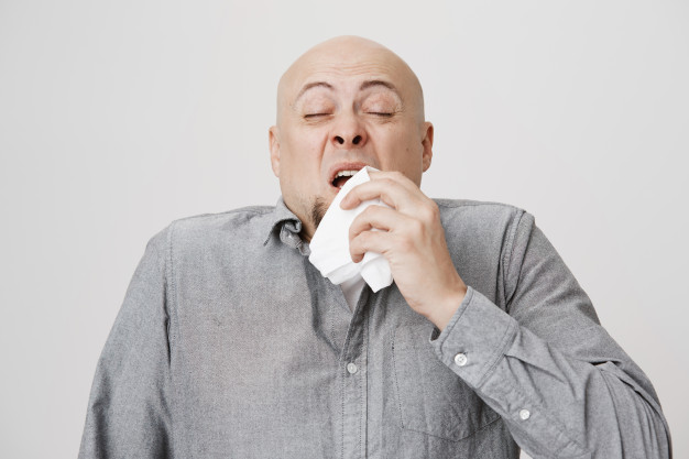 bald middle aged man sneezing in a napkin