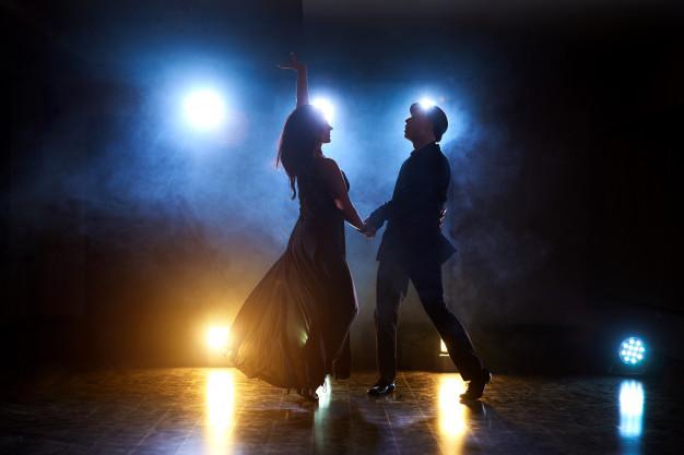 people dancing salsa in dark room