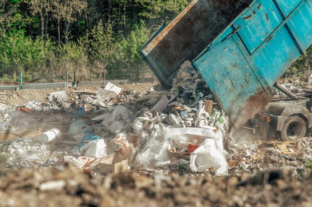 truck dumps trash into land