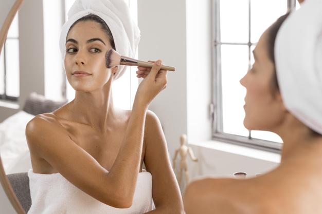 woman putting on natural makeup