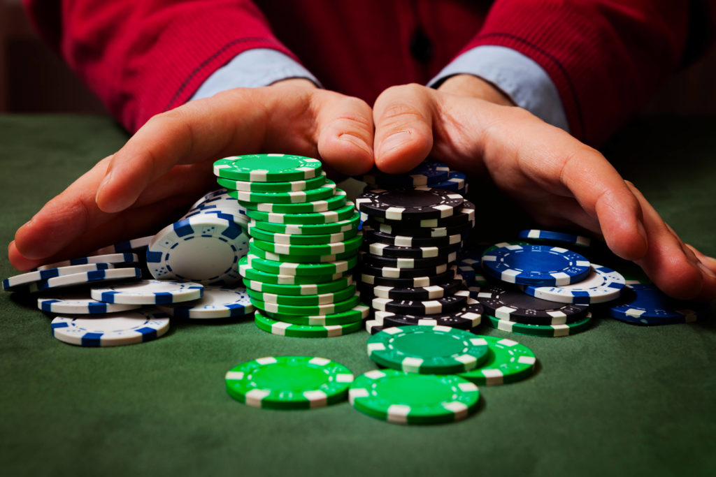 man holding poker chips while playing pokerin