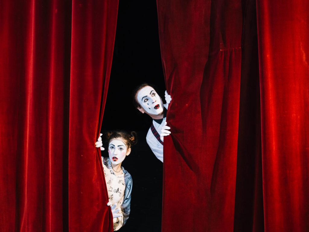 male female mime artist peeking from red curtain Tietopohja